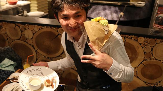 リクトへ修行に訪れた尾崎さんが花をもってピースサインをしている様子